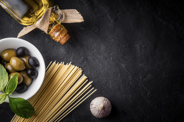 Spaghetti, olives and olive oil on the black stone table