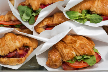 Croissants with salmon served in paper bags closeup