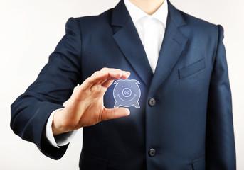 Businessman holding virtual piggy bank on light background