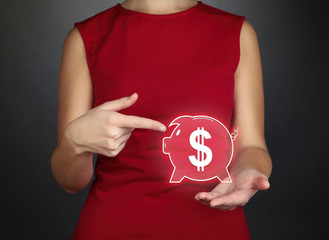 Female hands holding virtual piggy bank on gray background