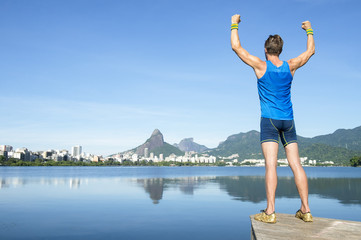Athlete in blue sport uniform standing with champion arms raised in front of Rio de Janeiro Brazil skyline at Lagoa Rodrigo de Freitas lagoon