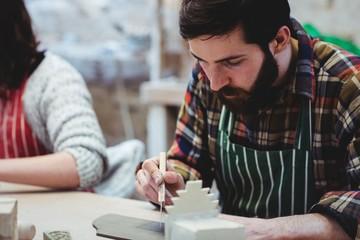 Focused bearded man working at workshop