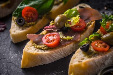 Slices of ciabatta with olives , tomatoes and basil on the black stone table horizontal