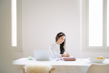 Young woman at table working at home on laptop