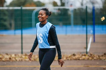 Young female netball player on netball court