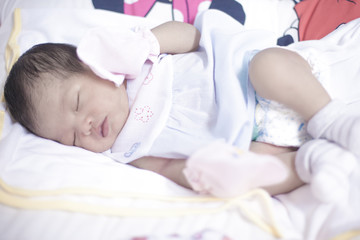 Newborn girl sleeping in her bed