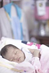 Newborn girl sleeping in her bed