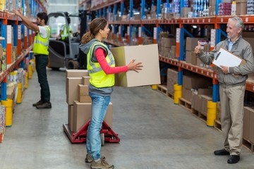 Manager looking a worker holding cardboard boxes with thumbs up