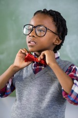 Thoughtful schoolboy adjusting a bow tie in classroom