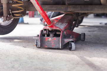 Close up shot of old red car jack and removed wheel selective fo