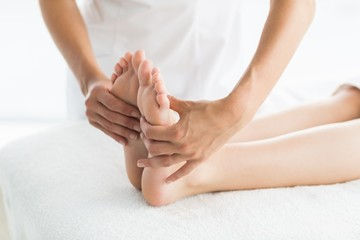 Cropped image of masseur giving foot massage to woman