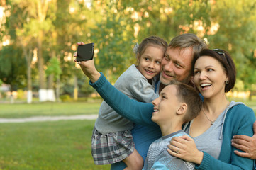 family taking selfie in park