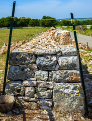 Restore drywall with stones wall in focus in the countryside of Apulia