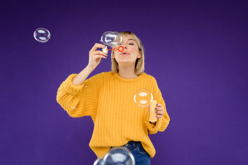 Portrait of young girl blowing bubbles over purple background.