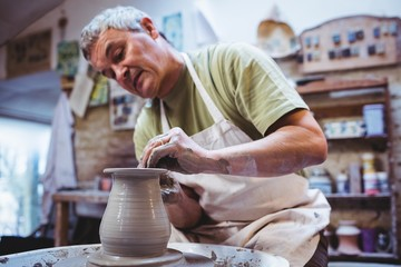 Craftsperson making container in pottery workshop