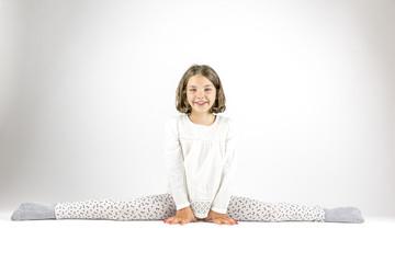 Cute agile girl sits in splits on floor, studio shot.