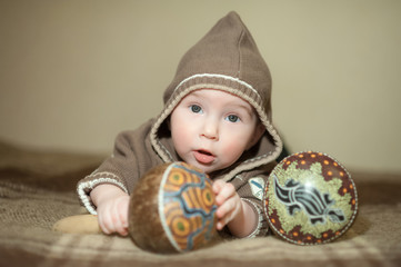 Cute baby playing on the bed, smiling and posing to camera