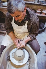 Mature artist preparing ceramic bowl