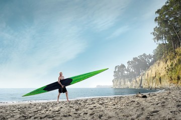 Surfer carrying surfboard onto beach, Santa Cruz, California, USA