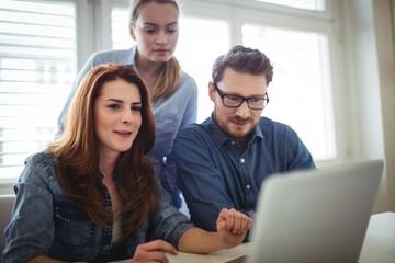 Confident businesswoman coworkers using laptop