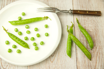 Pea pods and pea seeds on white plate