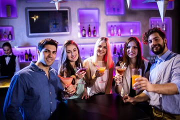 Group of friends showing cocktail at bar counter