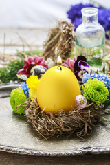 Candle in egg shape on the hay nest.