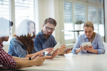 Business people using technologies in board room