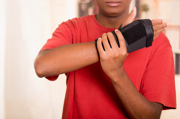 Man in red shirt wearing black wrist brace support on right hand and gripping arm with other
