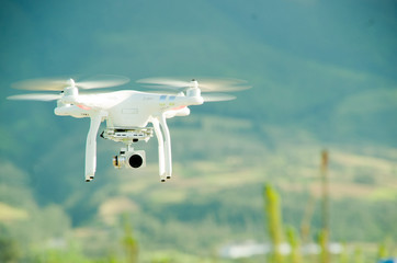 White drone with camera mounted underneath hovering midair, mountain landscape background