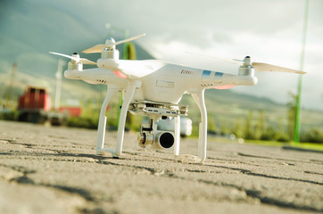 White drone with camera mounted underneath sitting on concrete surface, mountain landscape background