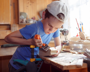 child whittling a  carpenter's plane. young carpenter working in a workshop