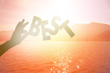 "silhouette of a hand holding ""BEST"" paper text with sunset at da"