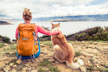 Woman hiker with dog looking at sea