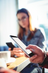 Close-up of man using cellphone with woman at cafe