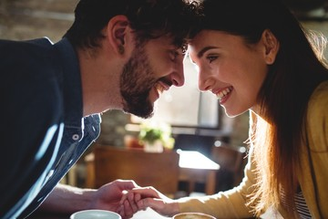 Side view of cheerful couple looking at each other in cafe