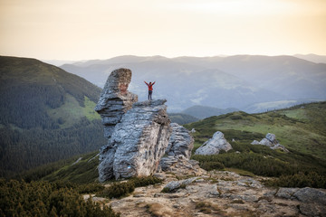Man standing on rock in mountains. Hands up scene.