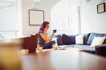 smiling woman holding a cup of coffee and take a phone call