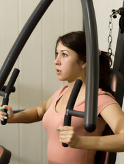 young woman is engaged in sports and gymnastics in the gym