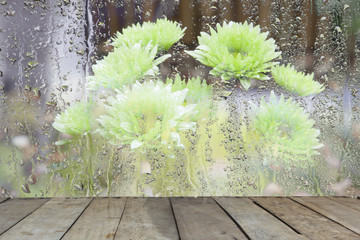 breezy.A bouquet of flowers behind glass wet with wood,