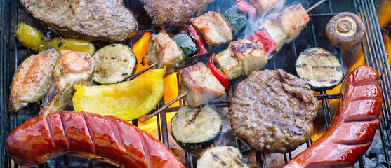 Geassorteerd vlees met groenten koken op een grill met vlammen