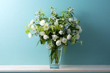 青い背景と白い薔薇とブルースターとスマイラックスと花瓶