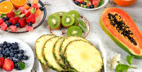 Preparing  fresh fruit salad on white wooden  background.