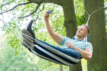 Man Lying In Hammock Taking Picture