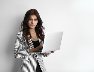 A Beautiful young Indian woman working on laptop against a white