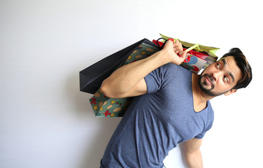 A young Indian man holding shopping bags on white background.