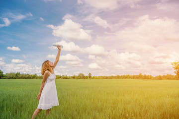 Woman drinking water on green meadow background.blue sky.