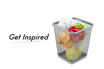 """conceptual image with word """"GET INSPIRED"""" over crumple paper in metal dustbin and isolated white background"""