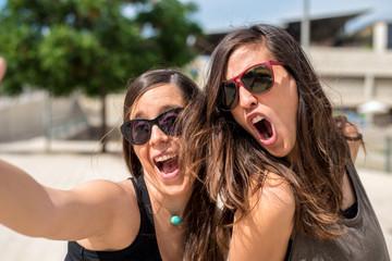 Two young women having fun while taking selfie
