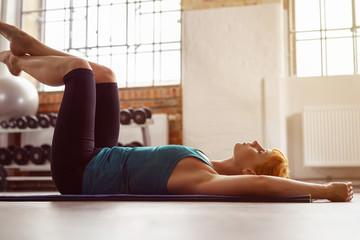 frau im fitnessstudio entspannt die muskulatur nach dem training